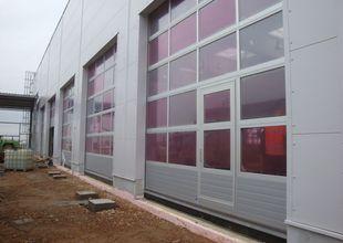 Sekční vrata s integrovanými dveřmi do prostoru autoservisu