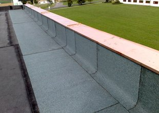 Detail atiky (oplechování a pokládka vrchní vrstvy střešní krytiny z modifikovaných asfaltových pásů)